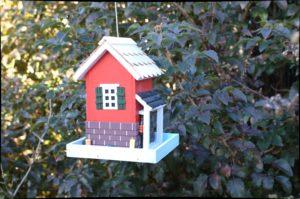 miejsce na karmnik dla ptaków czerwony domek w ogrodzie