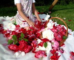 Kwiaty, płatki, koszyk i dziewczynka na kocu w ogrodzie