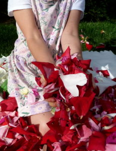 Dziewczynka trzyma garść płatków róż