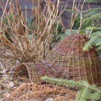 domek dla jeża koło krzaków hortensji w ogrodzie