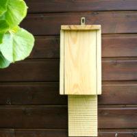 Budka dla nietoperzy z drewna na ścianie szopy w ogrodzie
