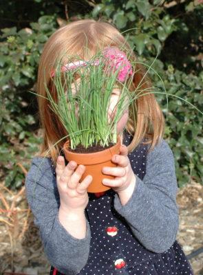 dzieci w ogrodzie szczypiorek w ceramicznej doniczce i dziecko