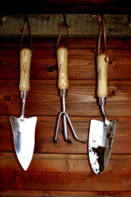 zestaw narzędzi ręcznych do ogrodu wiszący w szopie
