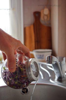 Wylewanie wody z kiełkownicy słoikowej przez sitko w zakręconej nakrętce